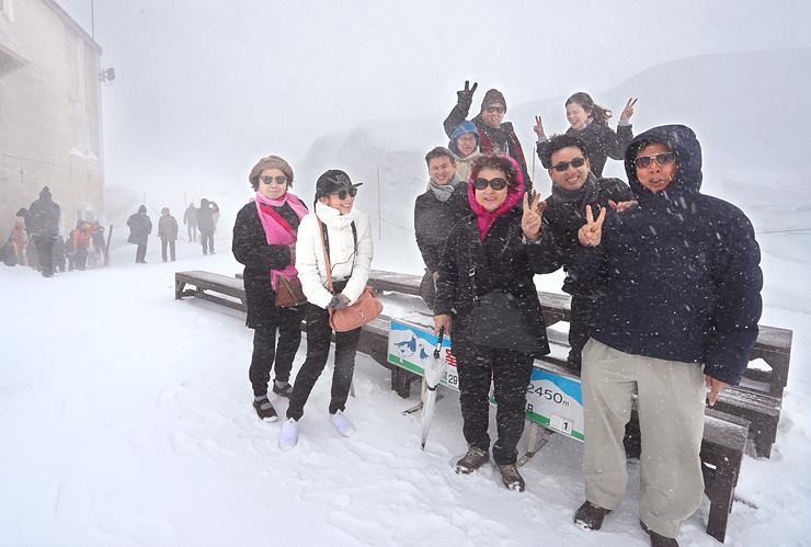 立山黒部アルペンルートが開通し、吹雪に負けず雪山の雰囲気を楽しむ外国人観光客ら=立山・室堂