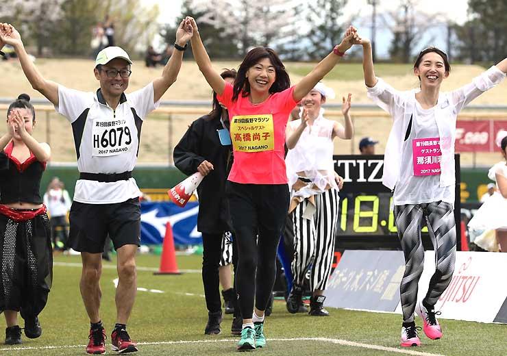 最後のランナーと手をつないでゴールを目指す高橋尚子さん(中央)=16日午後1時48分、長野オリンピックスタジアム