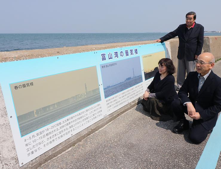 蜃気楼の解説板設置を喜ぶ大崎会長(右)ら=魚津市北中の海岸