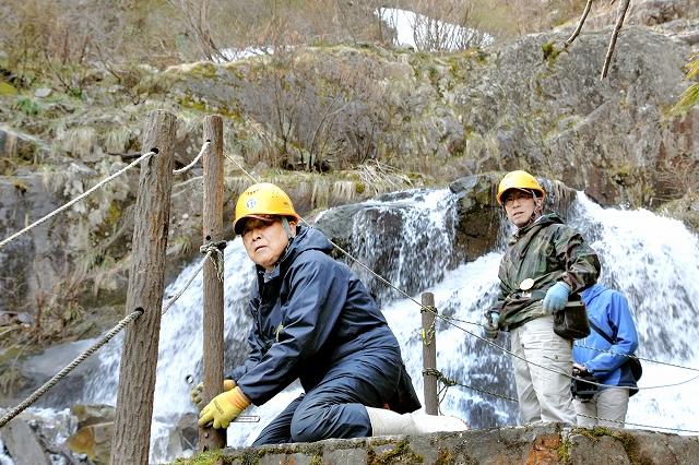 仏御前の滝の遊歩道に安全柵を取り付ける作業員=17日、福井県大野市仏原