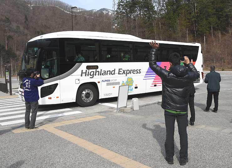 上高地に向かうシャトルバスに手を振る出発式参加者=17日、松本市安曇