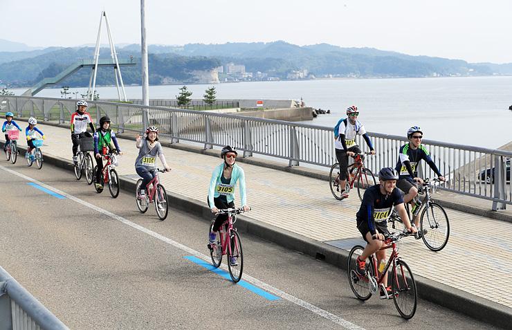 海沿いの景色を楽しみながら走る富山湾岸サイクリングの参加者=昨年7月、氷見市の比美乃江大橋