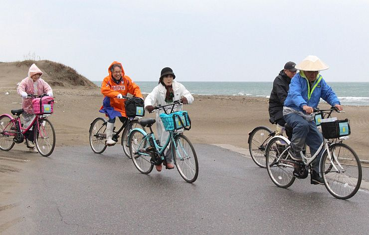 電動自転車をこいで角田山麓を巡る参加者=新潟市西蒲区角田地区