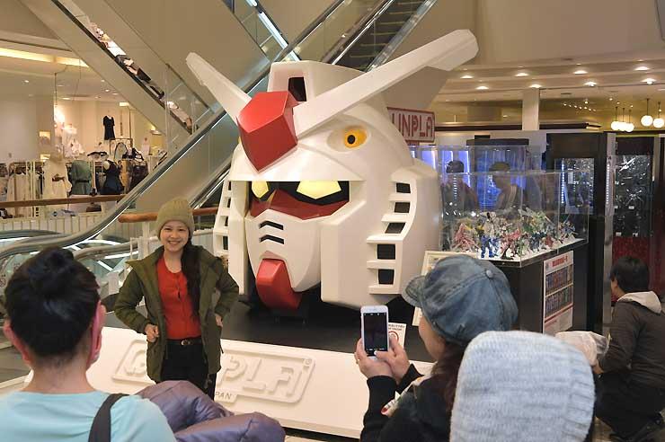 会場入り口のガンダムの頭部前で記念撮影する人たち=19日、松本市の松本パルコ