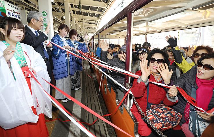 山の女神(左)や宇奈月温泉の女将らの見送りを受けて出発するトロッコ電車の乗客=黒部峡谷鉄道宇奈月駅