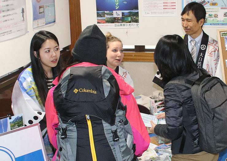 外国人観光客の問い合わせに応じる胡さん(左)とヘイリーさん(中央)=立山駅