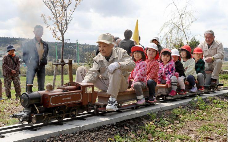 蒸気を上げて力強く走るミニSL。乗り込んだ子どもたちが笑顔を見せた=長岡市籠田の熊野神社