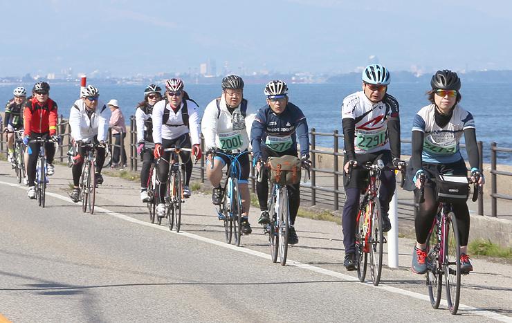 潮風を受け、海沿いの風景を楽しみながら自転車をこぐ参加者=魚津市青島