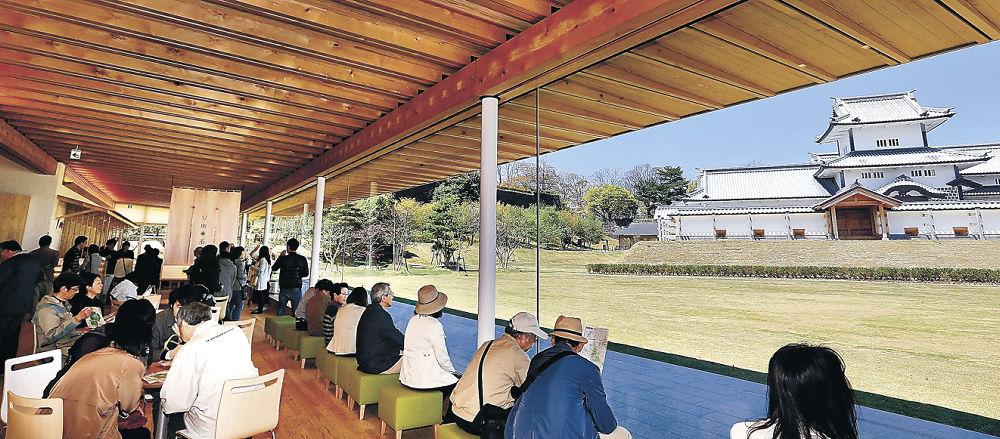 窓越しに橋爪門続櫓を眺める来館者=金沢城公園鶴の丸休憩館