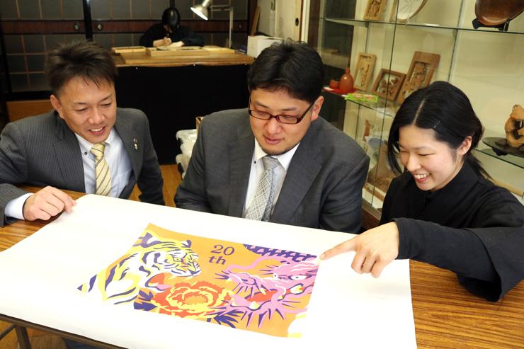 フラワーアートのデザインを確認する(左から)原野会長、石黒委員長、菊池さん