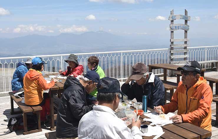 浅間山を望む美ケ原高原美術館の展望テラスで昼食を楽しむ人たち