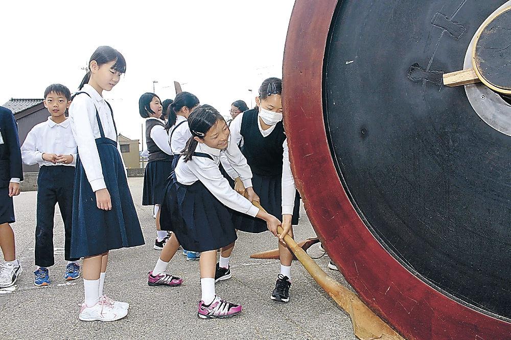 梃子を持って車輪を押す児童=七尾市の大地主神社