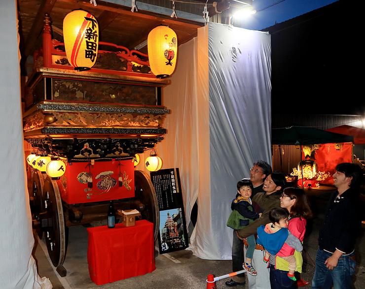 提灯の明かりで照らした曳山を前に29日の祭りを楽しみにする下新田町の住民=小矢部市新富町