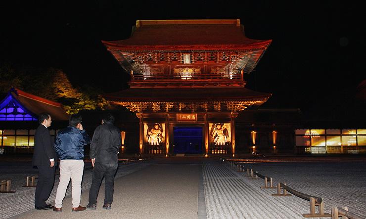 試験点灯で荘厳に浮かび上がった瑞龍寺の山門=高岡市関本町
