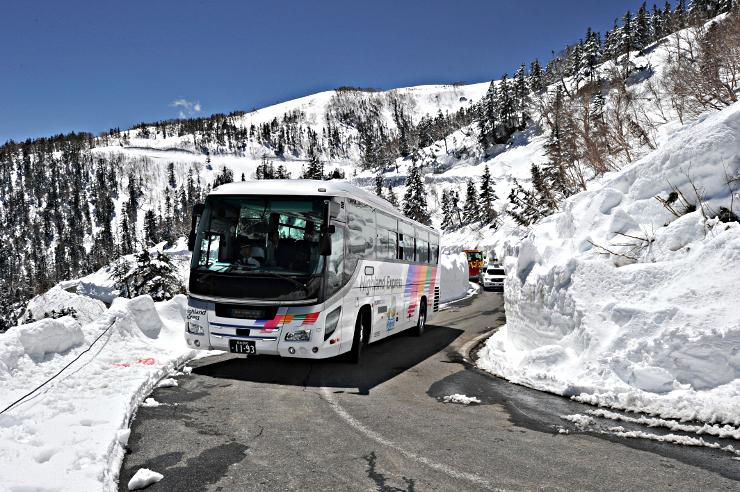 雪壁が残る県道を行く春山バス=28日、松本市安曇