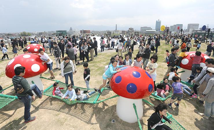 オープンした「オノマトペの屋上」でハンモック付きの「うとうと」など、八つの遊具で遊ぶ子どもたち=富山市木場町の富山県美術館