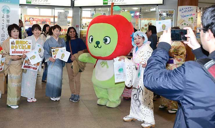 着物姿の「おもてなし隊」やアルクマと記念撮影する外国人旅行者(手前左から4人目)
