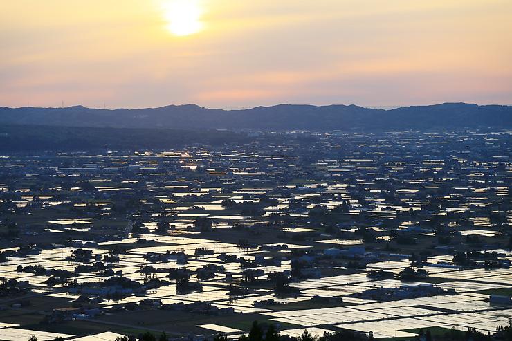 夕日に染まる散居村の水田=2日午後6時25分ごろ、砺波市庄川町隠尾の散居村展望広場近くから
