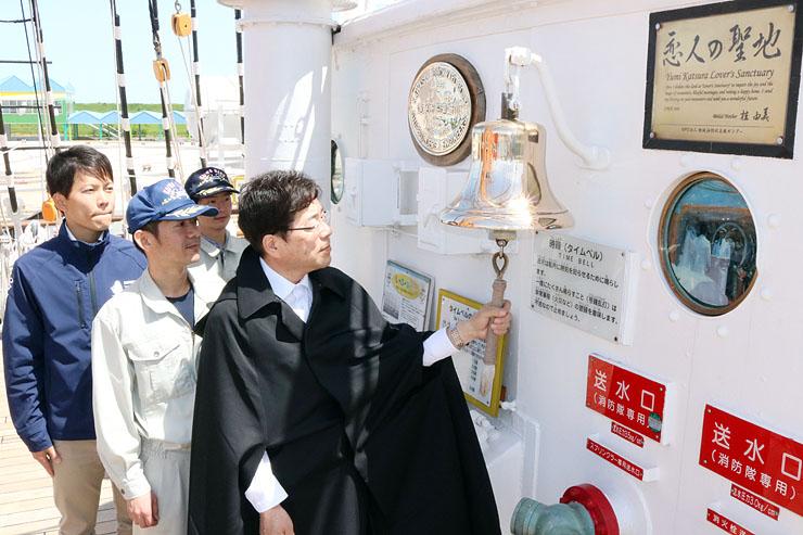 海王丸の甲板に設置されたタイムベルとマントを着けた財団職員ら=海王丸パーク
