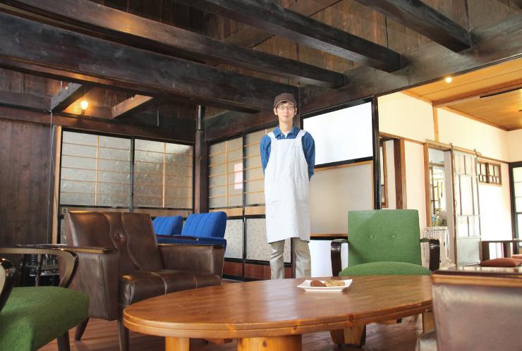 カフェの店内に立つ山浦さん。天井が吹き抜けで、広々としている