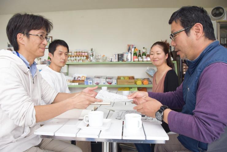 作品を監修する小山さん(手前右)に原稿を見せる鮱名さん(同左)。奥は右から前沢さん、田中さん