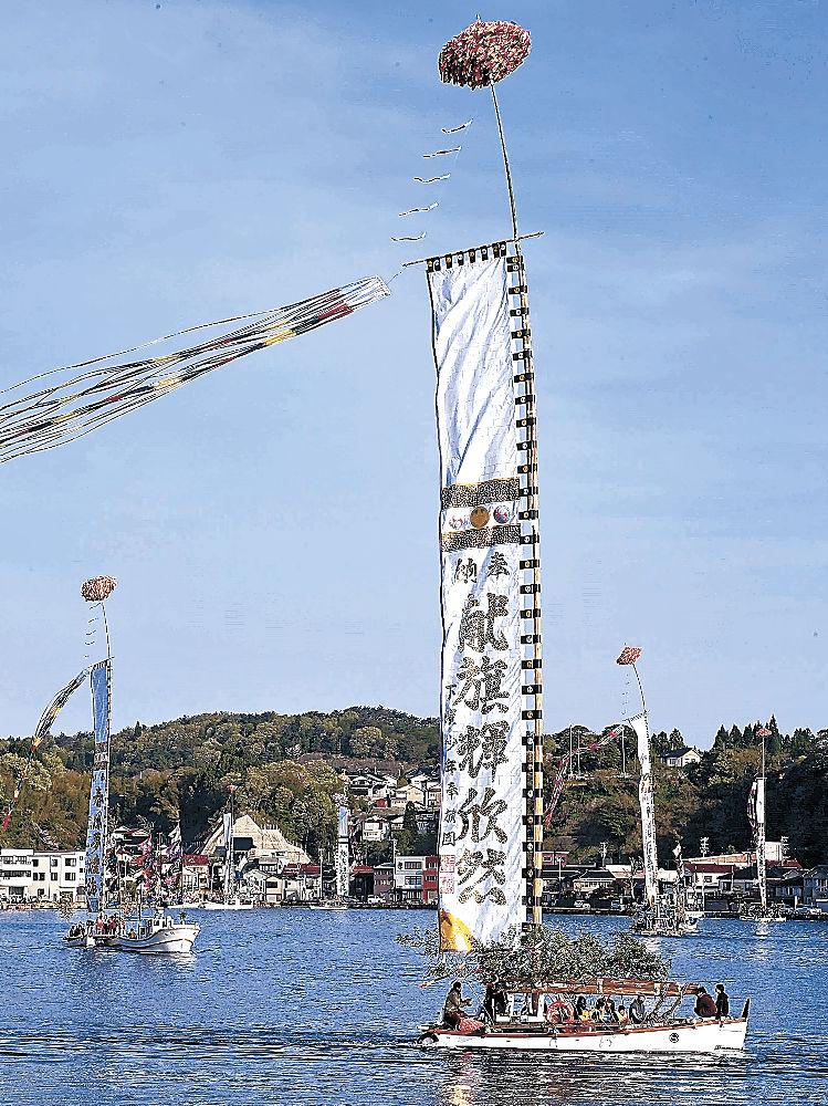 青空の下、とも旗をたなびかせて巡航する伝馬船=能登町小木港