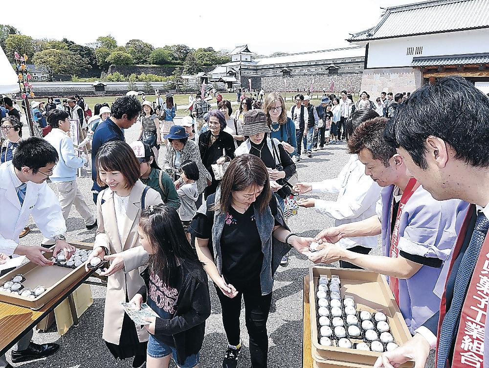 和菓子「珠姫てまり」の振る舞いに列をつくる来場者=金沢城公園