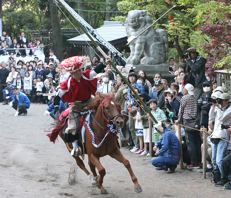 大勢の見物客が見守る中、疾走する馬から矢を射る武者姿の男性=下村加茂神社