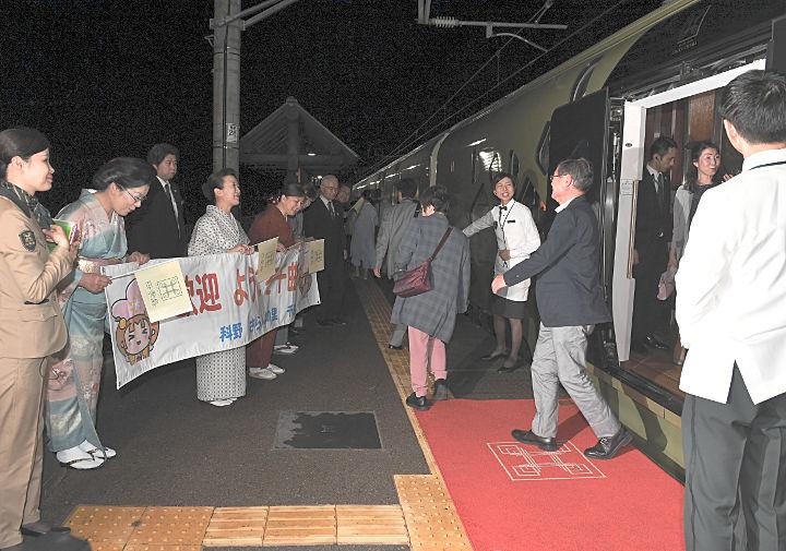 地元住民の歓迎を受けて姨捨駅に降り立つ「トランスイート四季島」の乗客たち=6日午後8時41分、千曲市