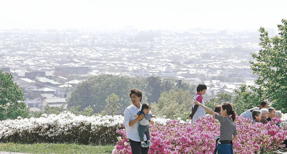 黄砂の影響でかすむ市街地を背にツツジを観賞する来園者=金沢市の大乗寺丘陵公園