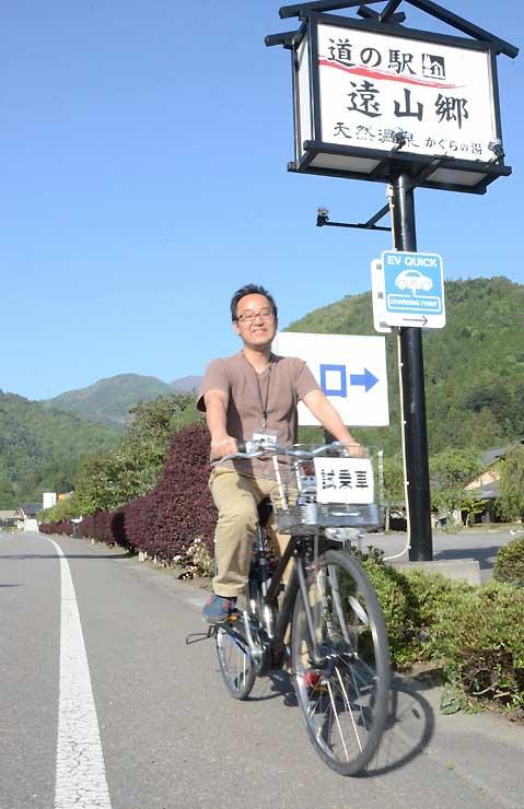 道の駅「遠山郷」前の国道152号を電動自転車で走る菅原さん