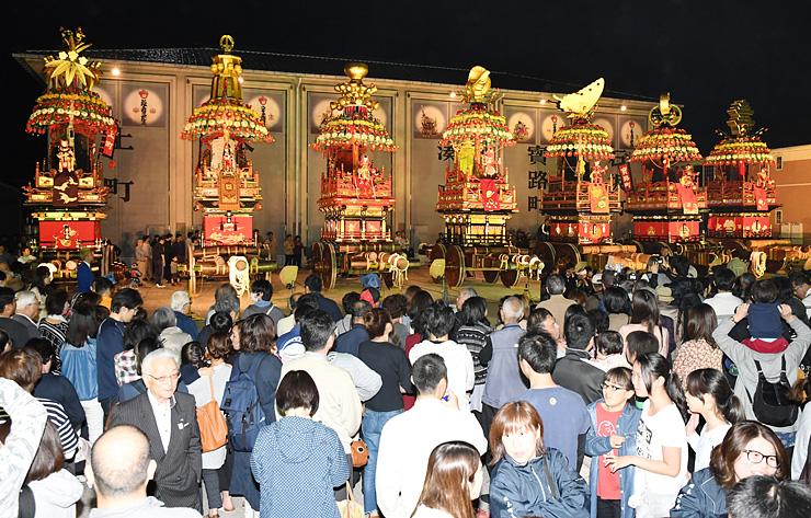 伏木曳山祭の本番を前にライトアップされた花山車。大勢の見物客が訪れた=高岡市伏木本町の山倉前