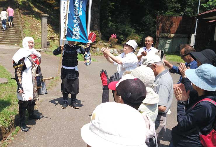春日山神社など上越市内を巡る昨年のバスツアーの様子。上越のおもてなし武将隊(左)が参加者を楽しませた