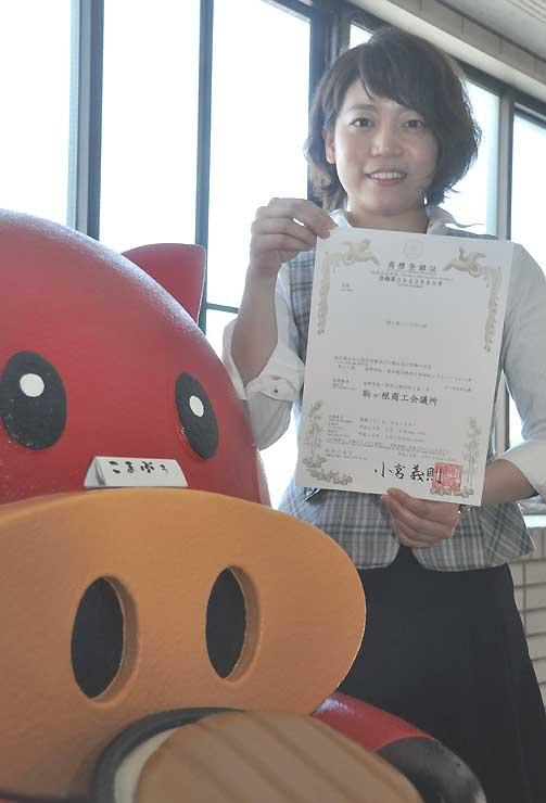 駒ケ根ソースかつ丼会のキャラクター「こまぶぅ」の横で登録証を手にする駒ケ根商議所職員