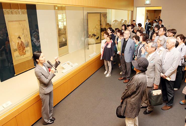 高田学芸員(左)の解説を聞きながら作品を鑑賞する来場者=県水墨美術館
