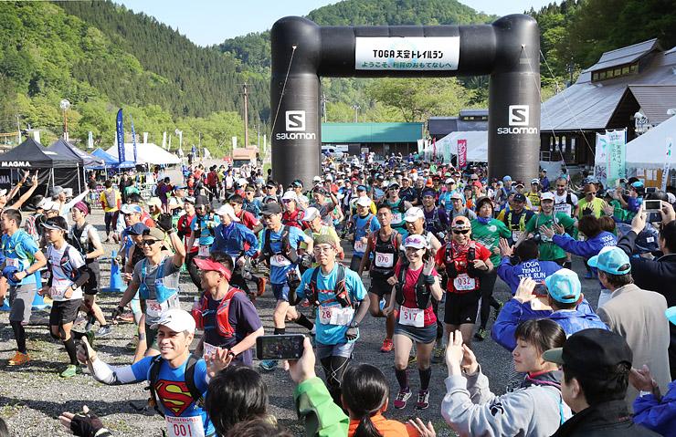 新緑の山々をバックにスタートするロングコースの参加者たち=利賀国際キャンプ場