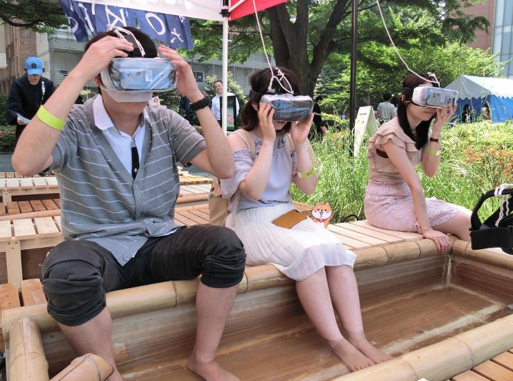 渋温泉の足湯でバーチャルリアリティーを楽しむ学生たち=東大本郷キャンパス