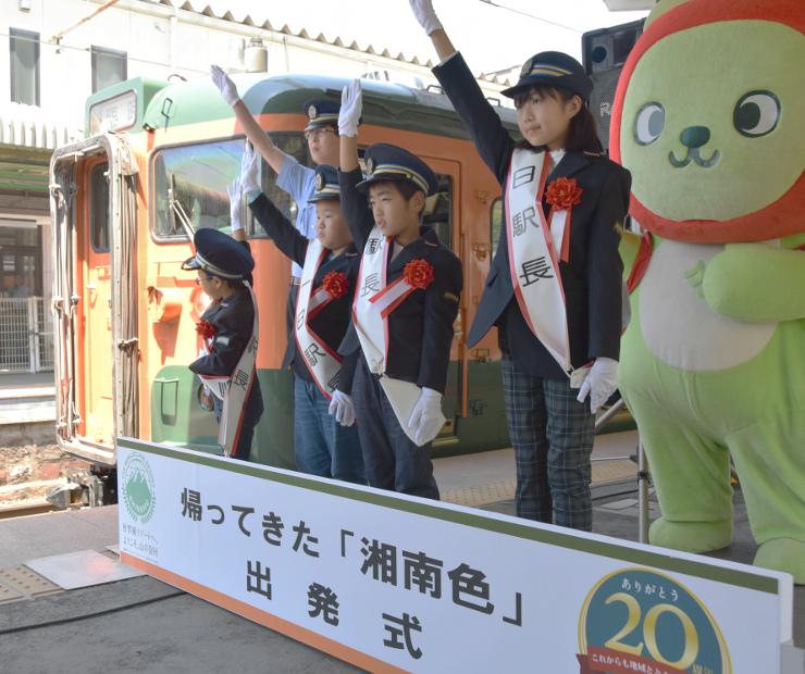 戸倉駅を出る「湘南色」の電車の横で出発合図をする子どもたち