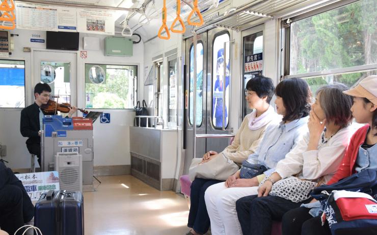 上高地線の車内でバイオリンを演奏する牛山さん(左奥)=20日、松本市