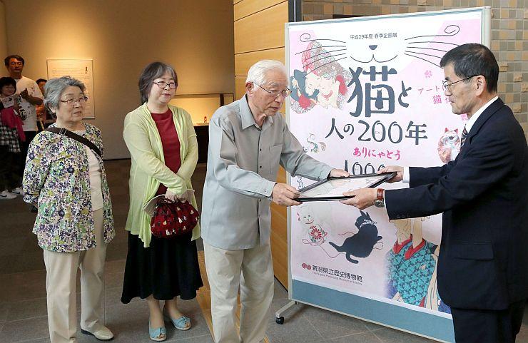 1万人目の認定証を受け取る男性=20日、長岡市の県立歴史博物館