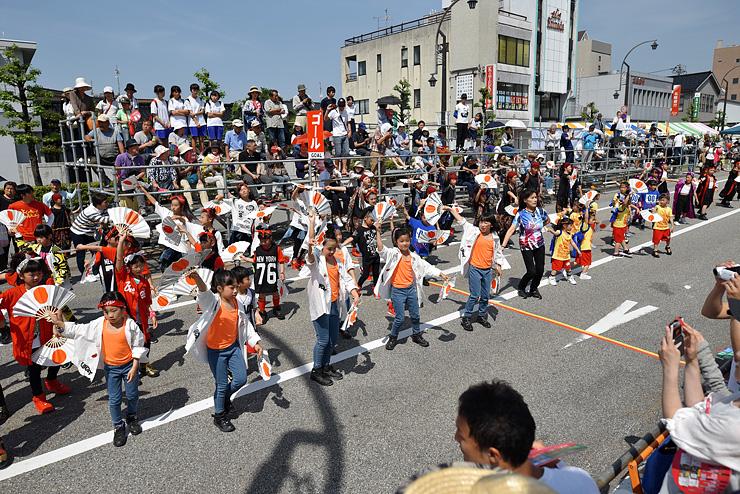 駅前通りで「よっしゃ来い !! CHOUROKU」を踊る大勢の子どもたち=あいの風とやま鉄道魚津駅前の通り