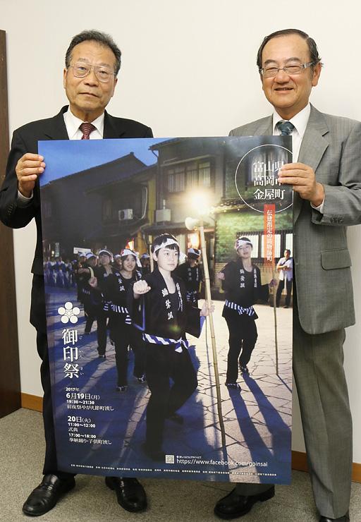 ポスターを手に御印祭をPRする田子会長(左)と松原事務局長=北日本新聞高岡支社