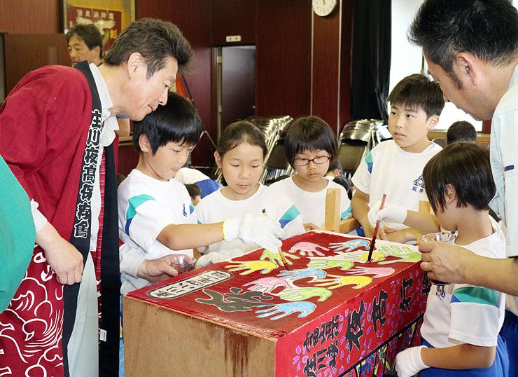 伏木会長(左)らに教わりながら、トッペ行燈に色を塗る児童