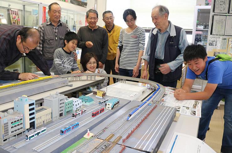 ジオラマの上を走る北陸新幹線の模型を眺める来場者=砺波市コミュニティプラザ