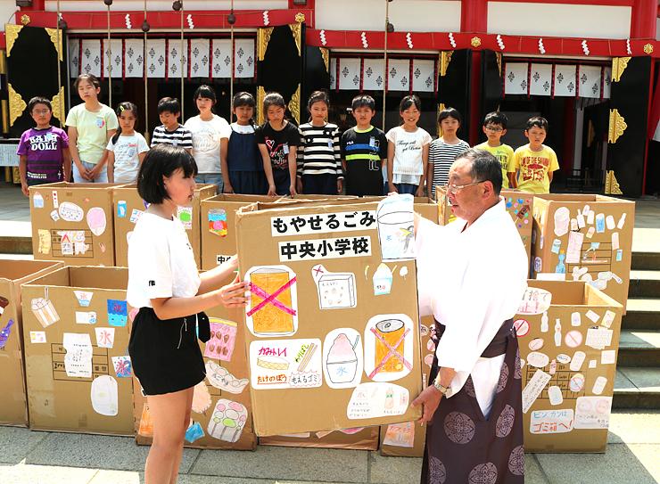 平尾宮司(手前右)に手作りのごみ箱を贈る児童