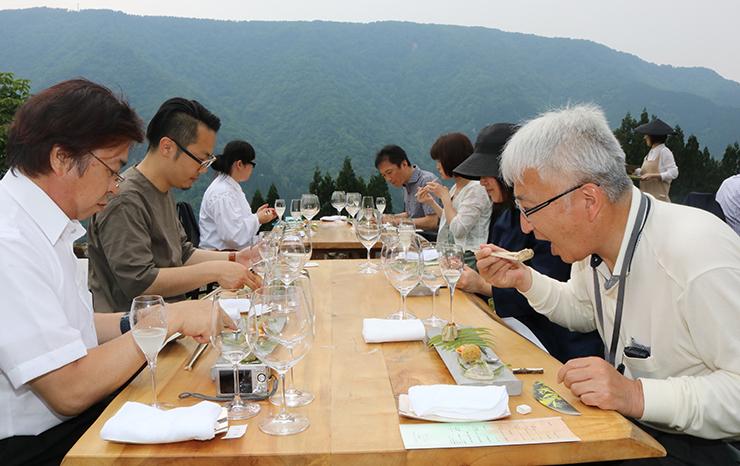 山々に囲まれた野外レストランで料理を堪能する来店客=瞑想の郷