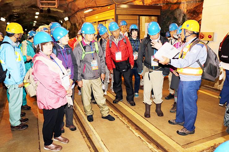 竪坑エレベーターの前で関電の社員の説明を聞く参加者=黒部峡谷欅平