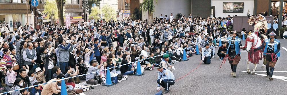 馬に乗って手を振る利家役の保阪さんに声援を送る大勢の見物客=金沢市香林坊1丁目