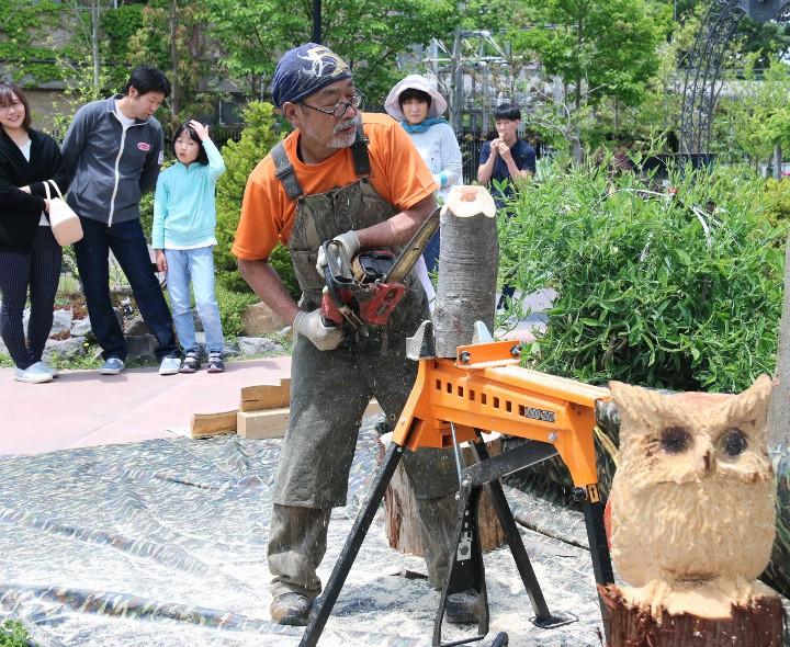 チェーンソーを使って木彫りのフクロウを作る饗場さん