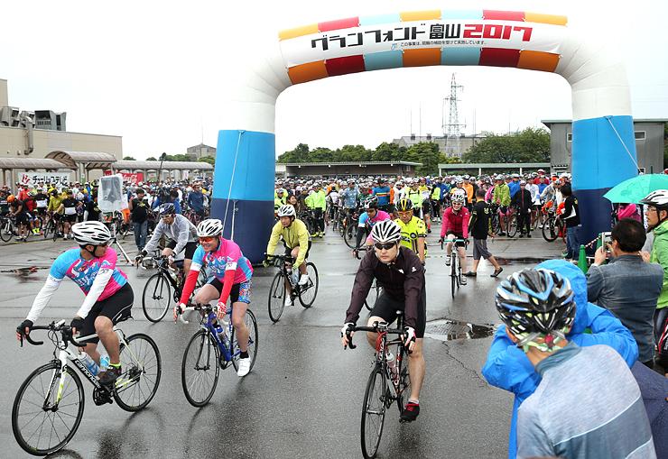 ゲートをくぐり抜けスタートするロングコースの参加者=富山競輪場
